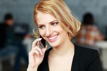 Cheerful blonde businesswoman talking on the phone in office