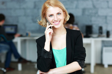 Young smiling businesswoman talking on the phone in office