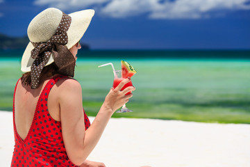 woman holding watermelon cocktail on the beach