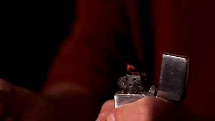 Hand lighting up a lighter on black background