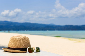 hat and sun glasses on tropical beach