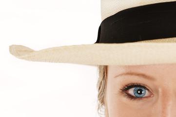 Frau mit blauen Augen trägt Strohhut