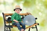 Kind sitzt auf der Bank und lacht poster