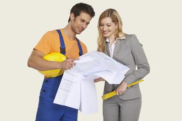 Bauarbeiter und Architekten suchen auf Blaupause