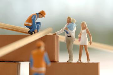 Figuren von Bauarbeitern und Familie auf der Baustelle