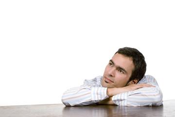 Junger Mann träumt, auf Tisch gestützt