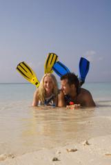 Malediven, Paar mit Schnorchelausrüstung am Strand