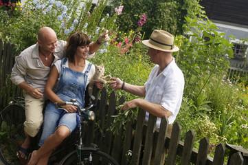 Paar sitzt auf dem Fahrrad im Gespräch mit dem Nachbarn am Zaun