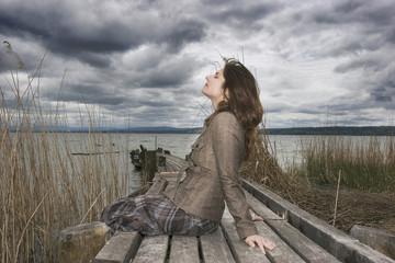 Frau sitzt auf Steg