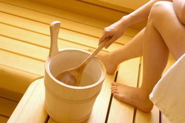 Frau mit Aufgusseimer in der Sauna