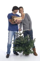 Paar mit Weihnachtsbaum und Brennholz
