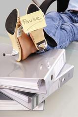 Frau bei der Arbeit mit Füßen auf Dokumenten