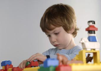 Junge spielt mit LEGO-Steinen
