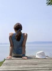 Junge Frau sitzt auf Steg