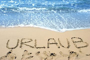 Das Wort Urlaub in den Sand am Strand geschrieben