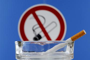 Aschenbecher mit Zigarette, Nichtraucher Schild im Hintergrund