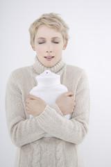 Frau mit Wärmflasche, die Augen geschlossen, Porträt