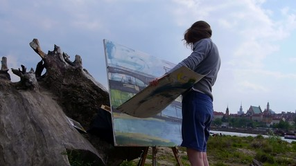 Woman paints a picture outdoors.