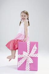 Mädchen sitzen auf Geschenk-Box, Lächeln, Portrait