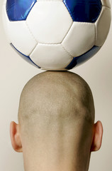 Mann mit Fußball auf den Kopf, Rückansicht