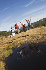 Österreich, Salzburger Land, Vier Wanderer am See springen in die Luft