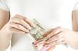 Frau, die Dollar-Noten in Portemonnaie steckt