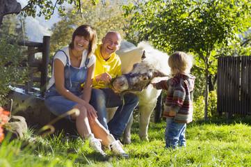 Eltern mit Kind im Garten, auch ein Pony ist dabei