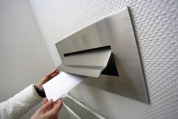 Menschliche Hand wirft Brief in Briefkasten