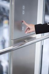 Hand einer Frau drückt Taste Tür öffnen im Aufzug