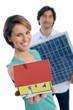 Paar halten Solarpanel und Haus