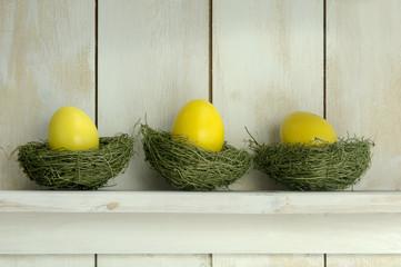 Gelbe Ostereier liegen im Regal auf Gras