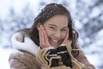 Frau im Schnee mit den Händen vorm Gesicht