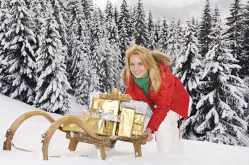 Österreich, Salzburger Land, Altenmarkt, junge Frau schiebt Schlitten mit Weihnachtsgeschenken
