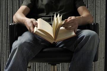 Man sitzt mit Buch in den Händen