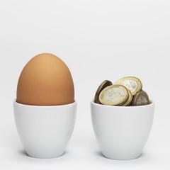 Ei und Euromünzen in Eierbecher, close-up