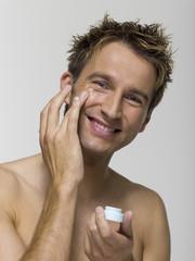 Junger Mann Gesichtscreme auftragen