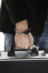 Mann mit Handschellen Geldkoffer tragen