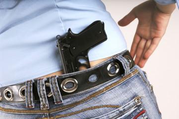 Frau mit Pistole in Jeans