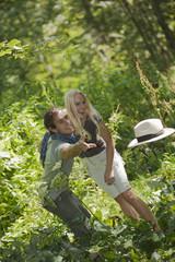 Junges Paar spielt mit Hut im Wald