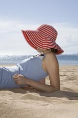 Frau liegt am Strand, Seitenansicht