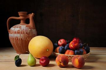 Ceramic carafe and various fresh fruits