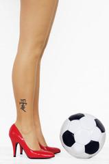Beine einer Frau, mit roten High Heels, Tattoo, steht vor einem Fußball