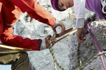 Deutschland, Bayern, junges Paar bereitet Kletterseil vor