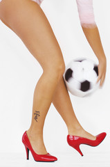 Frau mit roten High Heels spielt Fußball