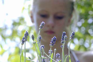 Junge Frau im Lavendelfeld, Fokus auf Lavendel Blumen im Vordergrund