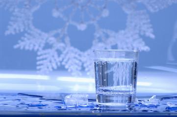Glas Wasser mit Eiswürfeln drumherum