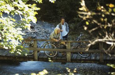 Paar mit Fahrrädern, stehend auf Holzbrücke, lächelnd