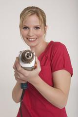 Frau jung mit einer Bohrmaschine