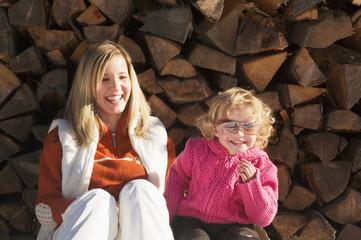 Mutter und Tochter sitzten vor Holzstapel