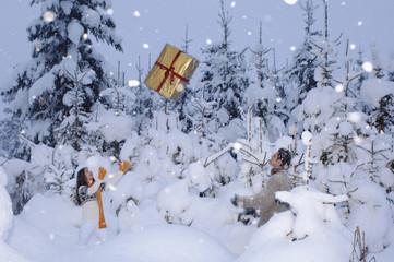 Paar im Schnee, werfen sich Geschenke zu